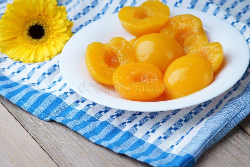 Pfirsiche im Sirup und in einem gelben gerber lizenzfreie stockfotos