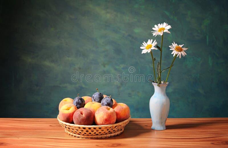 Pfirsiche und Pflaumen in den Weidenkörben und in den Blumen lizenzfreies stockbild