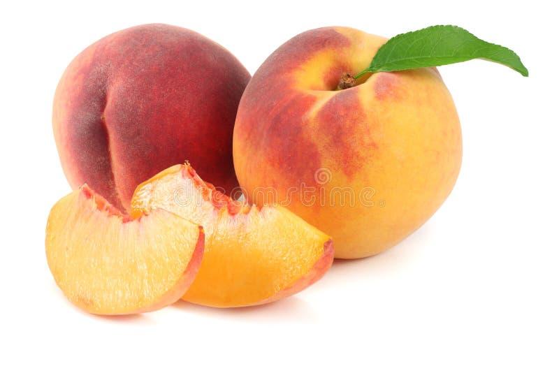 Pfirsichfrucht mit grünem Blatt und Scheiben lokalisiert auf weißem Hintergrund lizenzfreies stockfoto