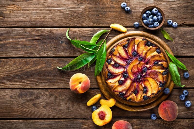 Pfirsichkäsekuchen oder -torte mit frischer Blaubeere auf hölzernem rustikalem Hintergrund, Draufsicht lizenzfreie stockfotografie