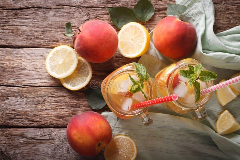 Pfirsichlimonade mit dem Eis und Minze nah oben in einem Glasgefäß horizo stockfoto