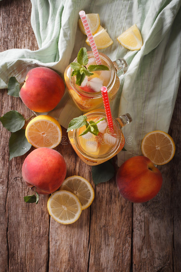 Pfirsichlimonade mit dem Eis und Minze nah oben in einem Glasgefäß Vertic stockfotografie
