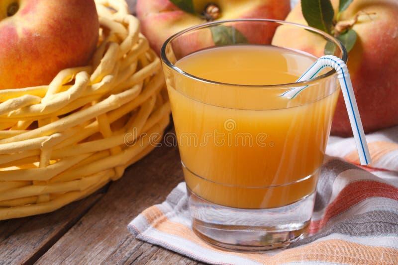 Pfirsichsaft in der Glasnahaufnahme auf einer Tabelle und einer Frucht horizontal stockfotos