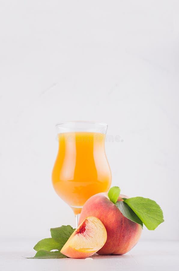 Pfirsichsaft im Eleganzglas mit saftigen Stückpfirsichen auf heller weißer hölzerner Tabelle, Kopienraum, Vertikale, Nahaufnahme stockfotografie