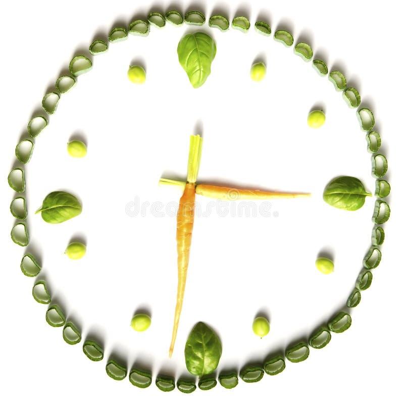Pflanzenkost des Gemüses in Form von Uhren, Frühlingszwiebeln, Karotten, Basilikum und Erbsen auf einem weißen Hintergrund lizenzfreie stockfotos