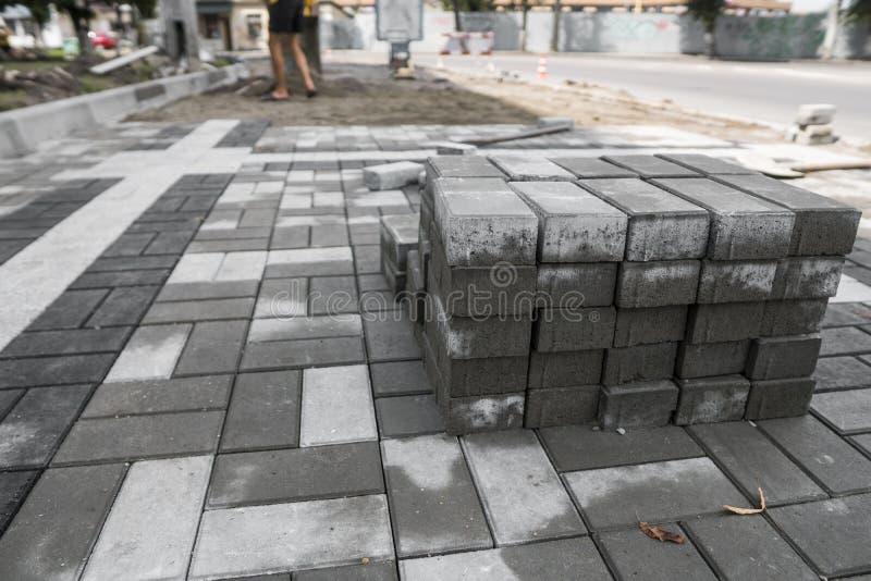 Pflasterungskopfstein im Stapel auf der Straße Graue quadratische Pflasterungsplatten des Betons oder des Granits für Bürgersteig lizenzfreie stockfotos
