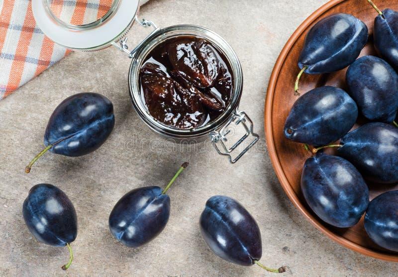 Pflaumenmarmelade in einem Glas und in blauen Pflaumen stockfoto