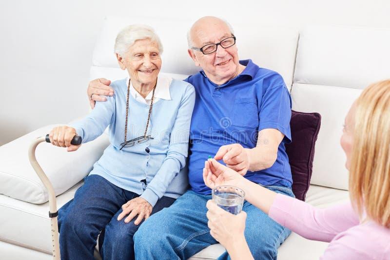 Pflegefrau gibt einem Senior eine Tablette lizenzfreie stockbilder