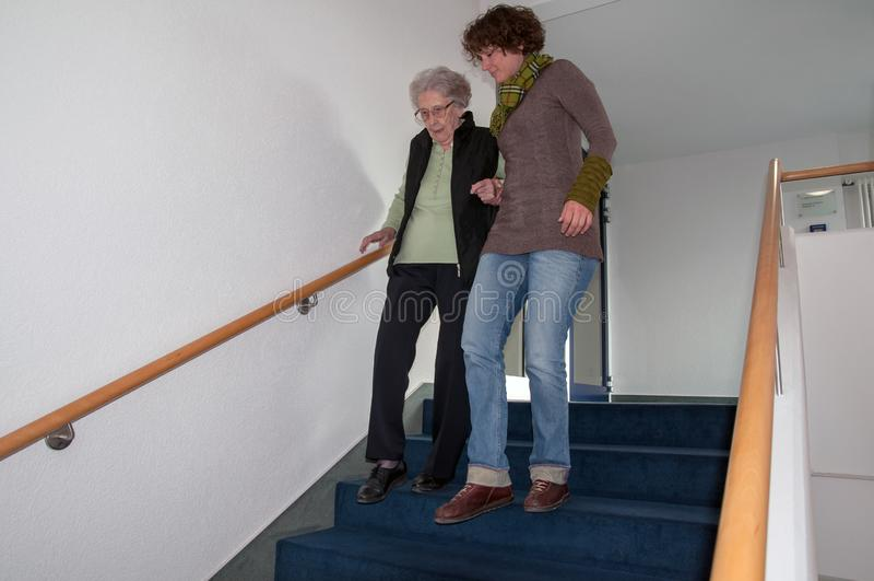 Pflegekraft, die der älteren Frau geht hinunter die Treppe hilft stockfotos
