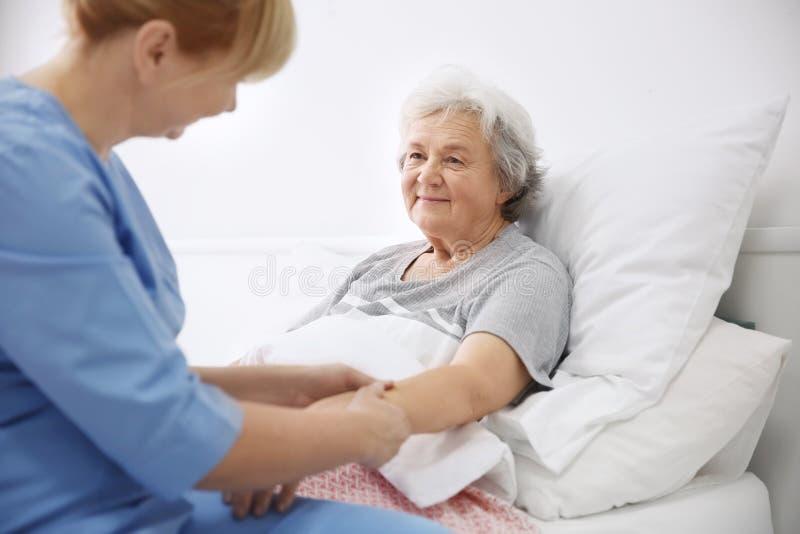 Pflegekraft, die Hand der älteren Frau massiert stockfoto