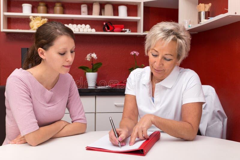Pflegekraft mit der jungen Frau, über Dokumente sprechend stockbilder