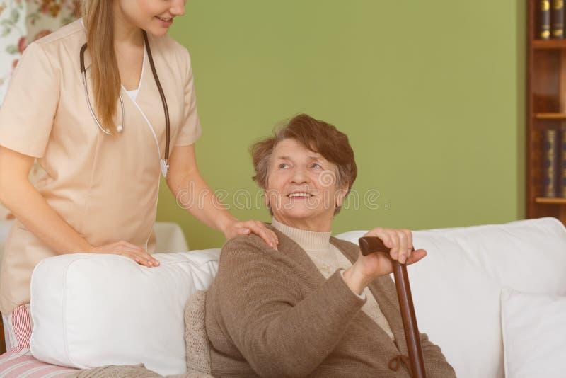 Pflegekraft und ältere Frau im Wohnzimmer lizenzfreie stockfotografie