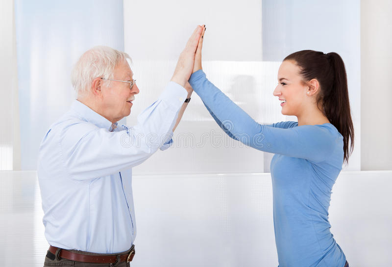 Pflegekraft und älterer Mann, die Hoch fünf geben stockbilder