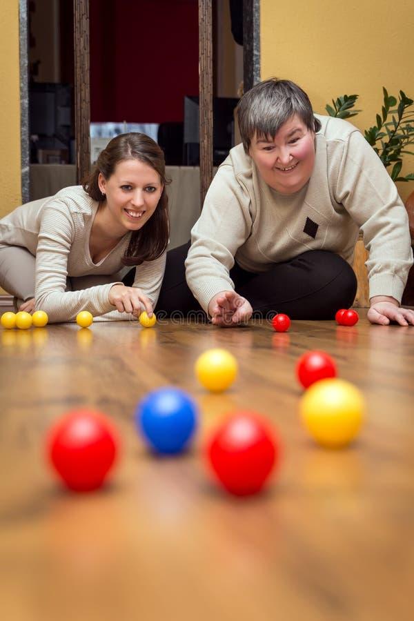 Pflegekraft und geistlich - behinderte Frau, die mit Bällen spielt lizenzfreie stockbilder