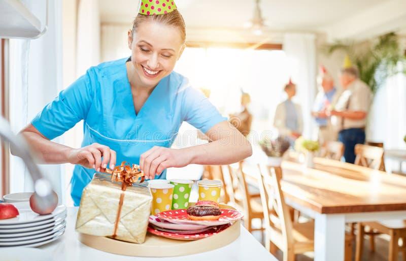 Pflegekraft verpackt Geschenk für Senioren lizenzfreies stockfoto