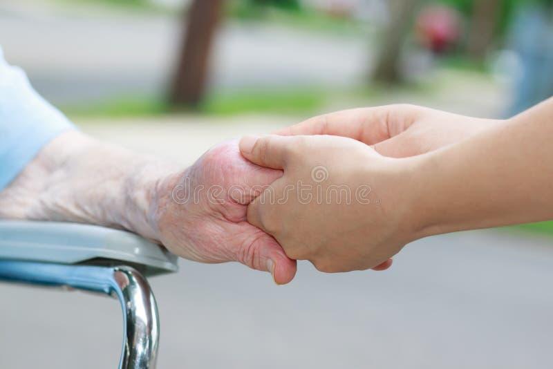 Pflegekraft, welche die Hand der älteren Frau hält stockfotografie