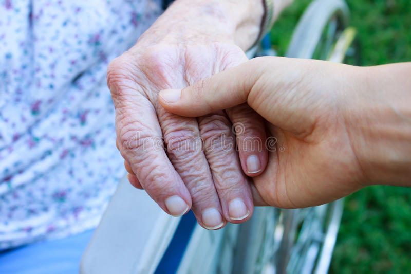 Pflegekraftholdingälterhand lizenzfreie stockfotografie