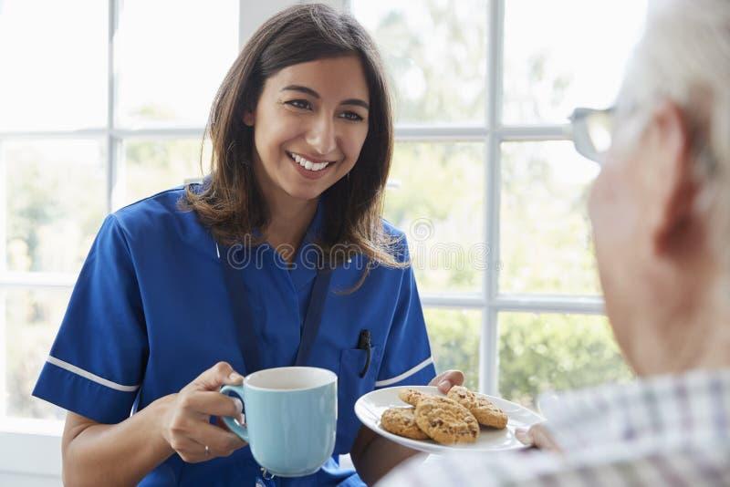 Pflegen Sie Aufschläge Tee und Kekse zum Senior, über Schulteransicht lizenzfreies stockbild