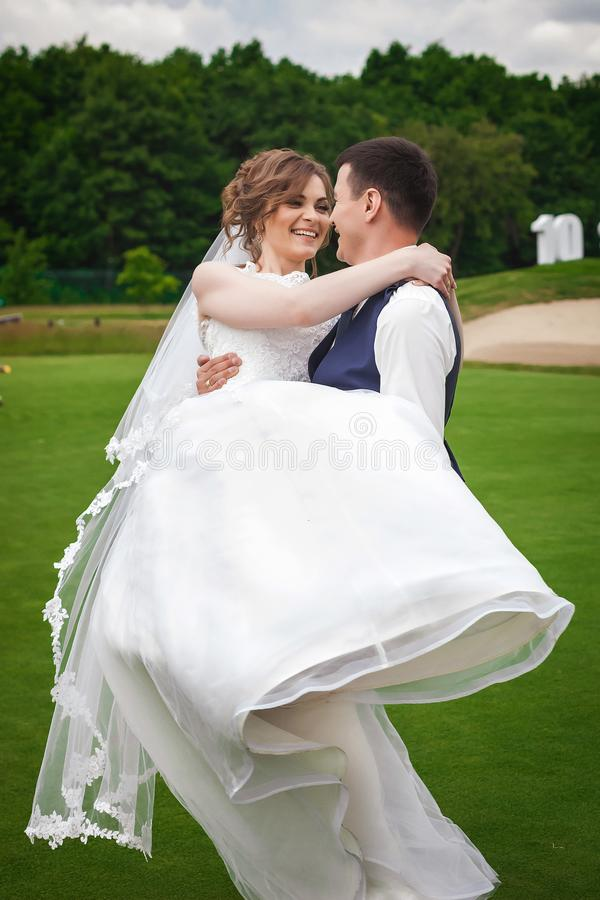 Pflegen Sie Braut auf Armen herum halten, mit ihr in der Natur umarmen und spinnen stockbild
