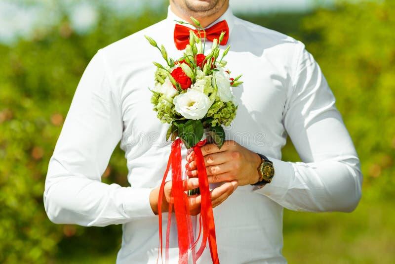 Pflegen Sie das Halten in den Händen empfindlicher, teurer, modischer Brauthochzeitsblumenstrauß von Blumen in Rotem und in weiße stockbild
