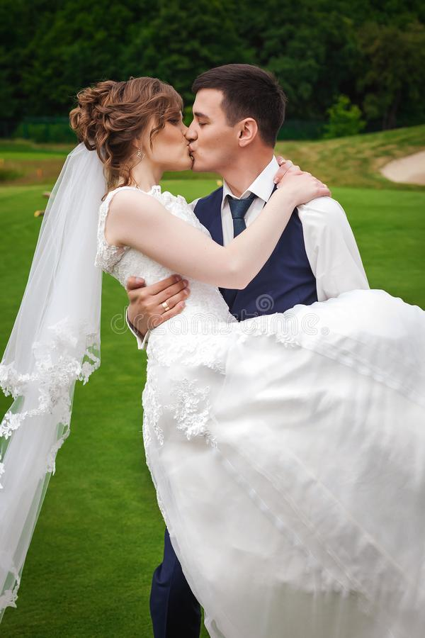 Pflegen Sie das Halten der Braut auf Armen, das Umarmen und das Küssen sie in der Natur stockfotos