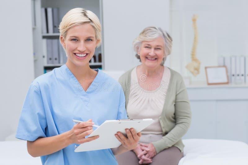 Pflegen Sie das Halten des Klemmbrettes während der weibliche Patient, der in der Klinik sitzt lizenzfreie stockfotos