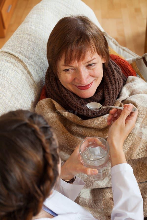 Pflegen Sie das Interessieren für kranke reife Frau im Raum stockfotografie