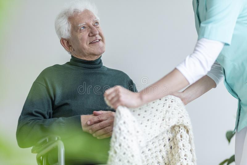 Pflegen Sie das Kümmern von  um glücklichem gelähmtem älterem Mann in einem Rollstuhl stockbild