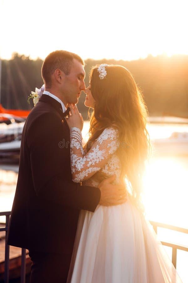 Pflegen Sie das K?ssen seiner Braut nahe dem See auf Sonnenuntergang stockfotos