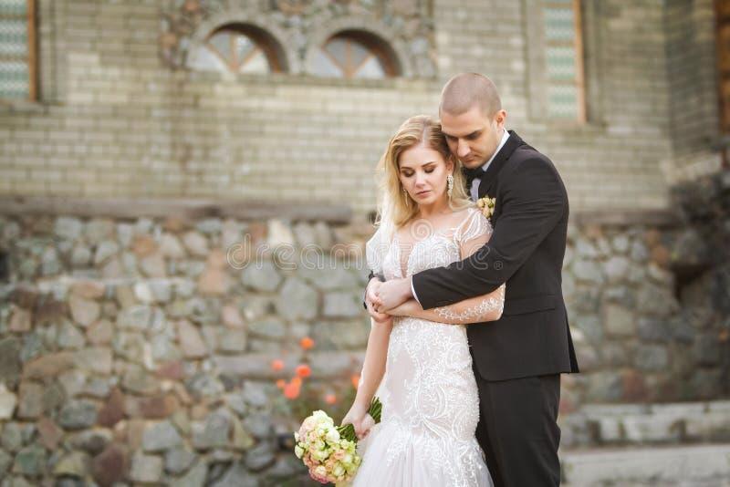 Pflegen Sie das Umarmen der Braut auf dem Hintergrund des Altbaus lizenzfreie stockfotografie