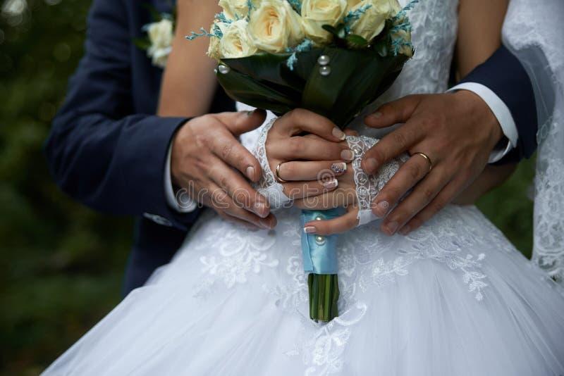 Pflegen Sie das Umarmen der Braut im weißen Kleid von hinten Blumenstraußnahaufnahme lizenzfreie stockfotografie