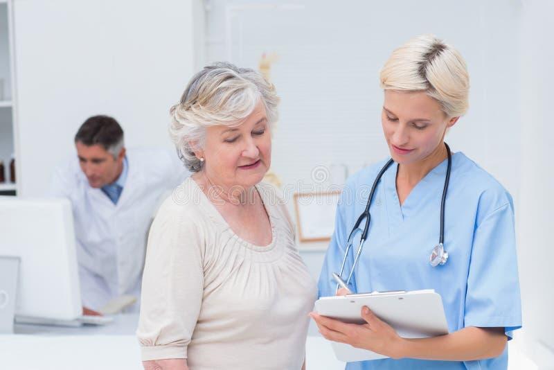 Pflegen Sie das Verständigen mit Patienten während Doktor, der Computer verwendet lizenzfreies stockfoto
