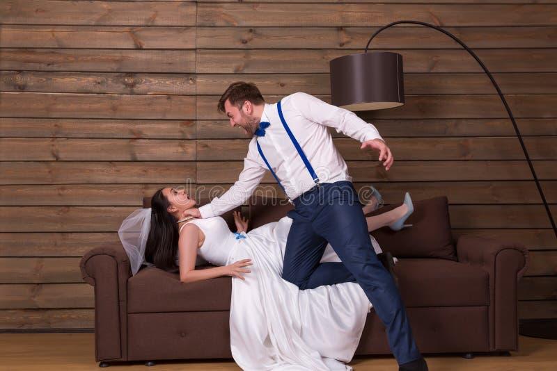 Pflegen Sie das Versuchen, Braut im weißen Kleid zu erdrosseln stockbilder