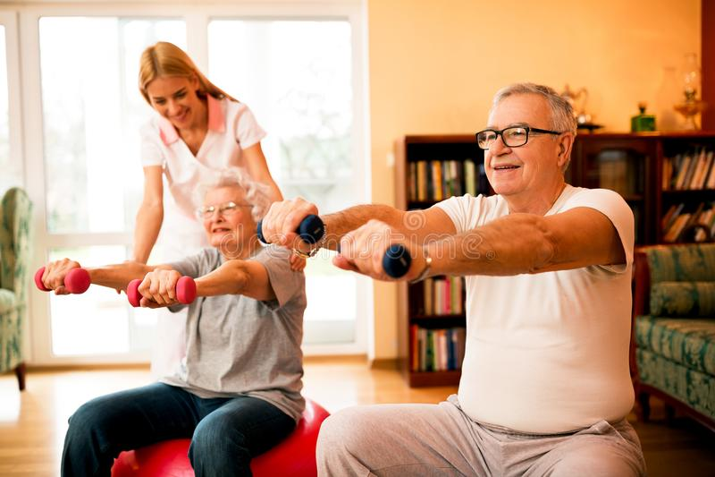 Pflegen Sie an den älteren Leuten der Krankenpflegehaushaltshilfen zum Handeln von Übungen stockfoto