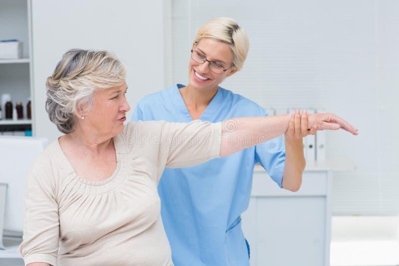 Pflegen Sie die Unterstützung des älteren Patienten beim Trainieren an der Klinik stockbild