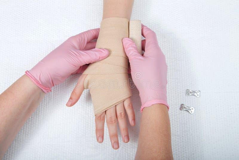 Pflegen Sie mit den rosa Handschuhen, die Hand der jungen Mädchen mit Asverband einwickeln stockfotos