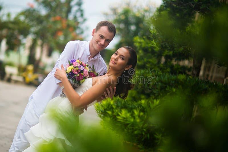 Pflegen Sie sich umarmte die Braut und lehnte sie etwas, um zu küssen Hochzeitspaarumarmen lizenzfreie stockbilder