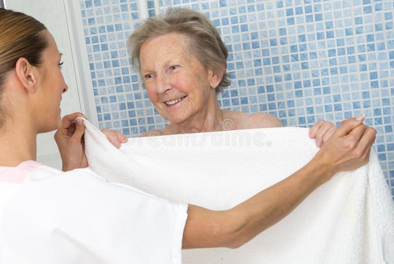 Pfleger oder Krankenschwester, die ältere Frau für Dusche unterstützen lizenzfreie stockfotos
