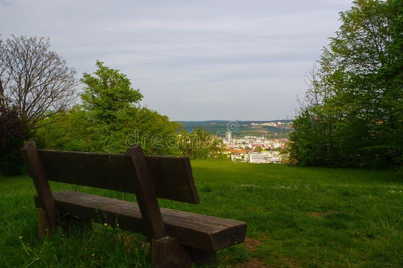 PFORZHEIM, DEUTSCHLAND - 29. APRIL 2015: alte Holzbank im Park auf Abhang mit Ansicht zur Stadt vom Wallberg-Schutt lizenzfreie stockfotografie
