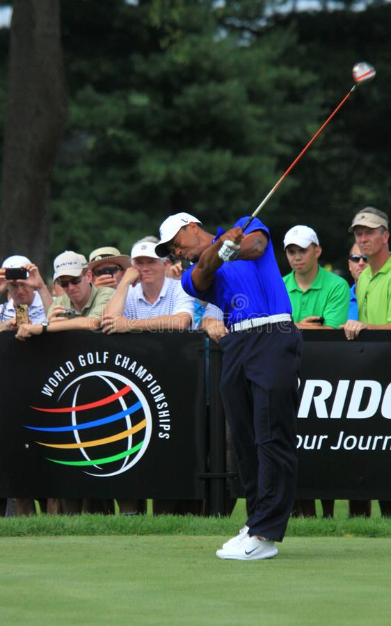 PGA champ Tiger woods. Tiger Woods extends his arms as he swings his club on the golf course stock image