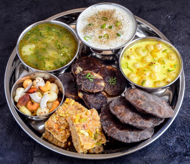 Phalihari Thali eaten during fasting in India. Phalihari Thali Indian Fasting Food. Dryfruits barfi,potato sabji,makhane kheer, raita,kuttu pakodi and Buckwheat royalty free stock images