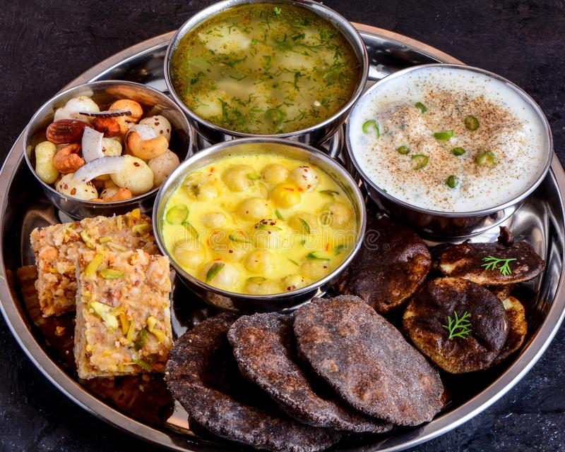 Phalihari Thali eaten during fasting in India. Phalihari thali indian fasting food. dryfruits barfi,potato sabji,makhane kheer, raita,kuttu pakodi and buckwheat stock images