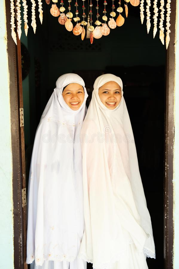 Portrait of two charming Muslim teenage girls in traditional clothing smiling at camera royalty free stock images