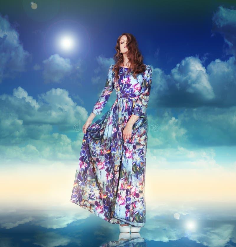 phantasie Frau im hellen Kleid schwebt unter Wolken stockfotografie