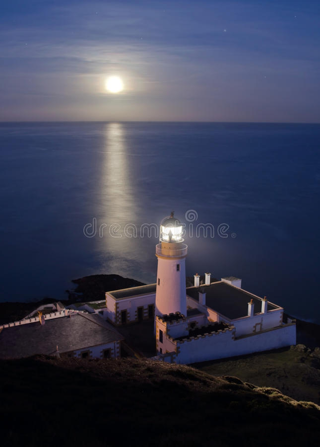 Phare avec la pleine lune se reflétant en mer photo stock