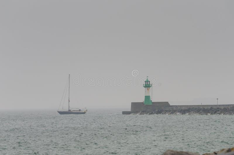 Phare avec le bateau dans le jour pluvieux, Sassnitz, Allemagne photos libres de droits