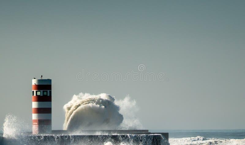 Phare avec une grande vague de l'eau avec le ciel bleu photo libre de droits