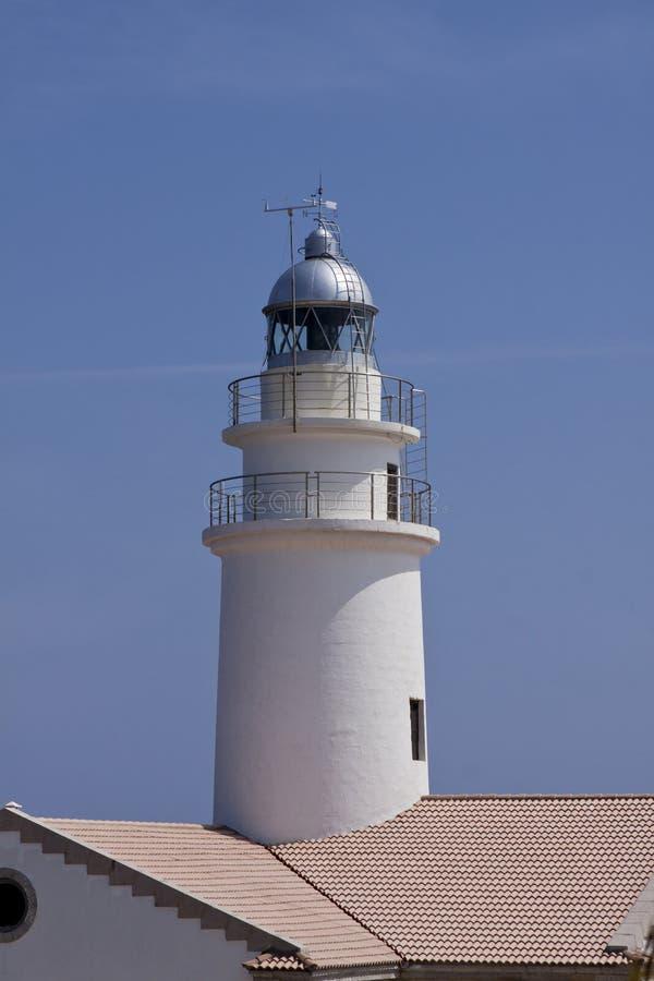 Phare blanc sur des roches dans le bleu de ciel de l'eau d'océan de mer photos stock