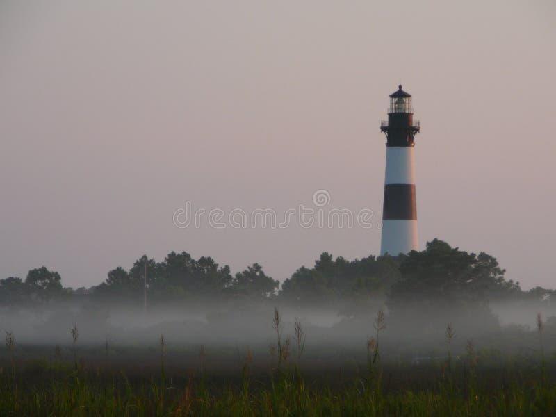 Phare dans le brouillard de matin image stock