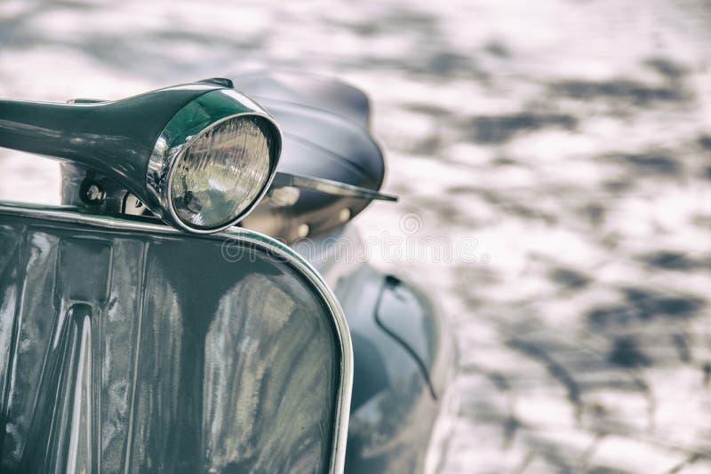 Phare de moto de style de film de cru Détail haut étroit du scooter d'une manière élégante conçu de cru garé dans une rue images libres de droits